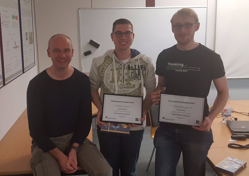 Picture of Prof. Dr.-Ing. habil. Falko Dressler, Julian Heinovski (B.Sc.) & Max Schettler (B.Sc.) after getting the Distinguished Student Award